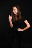Η στάση κοριτσιών σε ένα μαύρο φόρεμα γελά και κοιτάζει μακριά Στοκ Φωτογραφίες