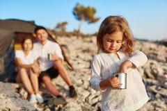 Η στάση κοριτσιών στην παραλία και η τοποθέτηση την παραδίδουν το φλυτζάνι Στοκ Εικόνες