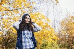 Η στάση κοριτσιών στο δάσος φθινοπώρου και ισιώνει το καπέλο Στοκ εικόνα με δικαίωμα ελεύθερης χρήσης