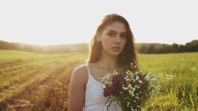Η στάση κοριτσιών στο λιβάδι με την ανθοδέσμη των άγριων λουλουδιών στο ηλιοβασίλεμα στο θερινό βράδυ, εξετάζει τη κάμερα φιλμ μικρού μήκους