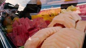Η στάση με τα φρέσκα τεμαχισμένα φρούτα, αγοραστές επιλέγει τα φρούτα για έναν φρέσκο χυμό απόθεμα βίντεο