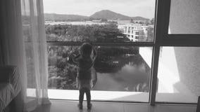 Η στάση μικρών κοριτσιών κοντά στο μεγάλο ευρύ παράθυρο και χαιρετίζει το αεροπλάνο που πηγαίνοντας στην προσγείωση Μονοχρωματικό απόθεμα βίντεο