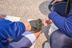 Η στάση που αιμορραγεί το δεξιό αγκώνα από το ύφασμα τριγώνων αυτοσχεδιάζει Στοκ Εικόνες
