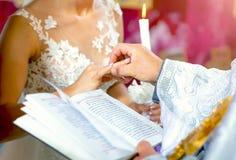Η στάση Newlyweds ενώπιον του ιερέα σε μια γαμήλια τελετή και ανταλλάσσει τα δαχτυλίδια στοκ εικόνες