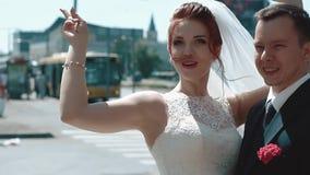 Η στάση Newlyweds στην πόλη, η νύφη χαίρεται, αυξάνει το χέρι της επάνω, κατόπιν αγκαλιάζει το νεόνυμφο, κλείνει επάνω απόθεμα βίντεο