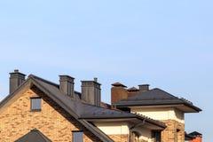 Η στέγη ενός εξοχικού σπιτιού με μια καπνοδόχο πετρών και ένα μπαλκόνι στοκ εικόνα