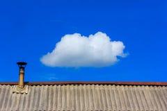 Η στέγη καλύπτεται με την πλάκα από την καπνοδόχο και ένα άσπρο σύννεφο στο μπλε ουρανό Στοκ Εικόνα