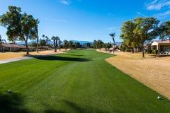 Η στενή δίοδος γκολφ είναι πράσινη που περιβάλλεται από καφετή τραχύ Στοκ εικόνα με δικαίωμα ελεύθερης χρήσης