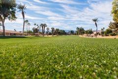 Η στενή δίοδος γκολφ είναι πράσινη που περιβάλλεται από καφετή τραχύ Στοκ φωτογραφία με δικαίωμα ελεύθερης χρήσης
