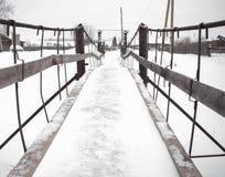 Η στενή χιονισμένη γέφυρα του μετάλλου και του ξύλου πέρα από τον παγωμένο χειμερινό ποταμό στο χωριό Στοκ Φωτογραφίες