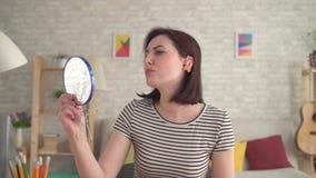 Η στενοχωρημένη νεολαία σκληρή της γυναίκας ακρόασης βάζει μια ενίσχυση ακρόασης στο αυτί της και κοιτάζει στον καθρέφτη φιλμ μικρού μήκους