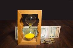 Η στιλπνή παλιή κλεψύδρα που στέκεται με τους αμερικανικούς λογαριασμούς δολαρίων στοκ φωτογραφίες