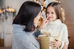 Η στοργική μητέρα δίνει το παρόν στη adorble μικρή κόρη της στοκ εικόνα με δικαίωμα ελεύθερης χρήσης