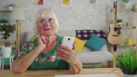 Η στοχαστική ηλικιωμένη γυναίκα βρίσκει μια λύση και χρησιμοποιεί μια συνεδρίαση smartphone στον πίνακα στο καθιστικό απόθεμα βίντεο