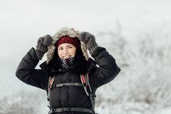 Η στοχαστική χαμογελώντας γυναίκα έντυσε θερμό βάζοντας μια κουκούλα επάνω Στοκ Εικόνα