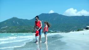 Η στρατοπέδευση, μια νέα οικογένεια, τα παιδιά και η μητέρα περπατούν κατά μήκος της ακροθαλασσιάς θαλασσίως, η μητέρα παρουσιάζε απόθεμα βίντεο