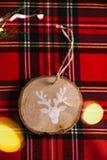Η στρογγυλή ξύλινη διακόσμηση με το σχέδιο ενός ταράνδου, στο κόκκινο ελεγμένο τραπεζομάντιλο και τα φω'τα, υπόβαθρο Χριστουγέννω στοκ εικόνες