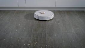 Η στρογγυλή σύγχρονη ρομποτική ηλεκτρική σκούπα κινείται στο πάτωμα σε ένα σπίτι και συλλέγει τα απορρίματα, έξυπνο σπίτι φιλμ μικρού μήκους