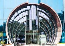 Η στρογγυλευμένη βερνικωμένη είσοδος με την περιστρεφόμενη πόρτα στο σύγχρονο ουρανοξύστη, κλείνει επάνω στοκ φωτογραφίες με δικαίωμα ελεύθερης χρήσης