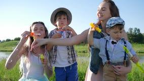 Η συγκίνηση της χαράς, γελώντας παιδιά που φυσούν το σαπούνι βράζει χαλαρώνοντας στη φύση απόθεμα βίντεο