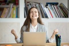 Η συγκινημένη γυναίκα σπουδαστής που αισθάνεται τον πλήρους ευφορίας εορτασμό κερδίζει on-line το s στοκ εικόνες