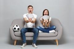 Η συγκινημένη ευθυμία οπαδών ποδοσφαίρου ανδρών γυναικών ζευγών υποστηρίζει επάνω την αγαπημένη ομάδα, που κρατά τον ανεμιστήρα τ στοκ φωτογραφίες