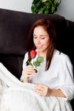 Η συγκινημένη νέα γυναίκα με ένα κόκκινο αυξήθηκε Στοκ Φωτογραφίες