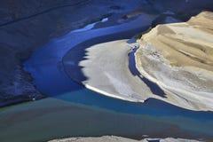 Η συμβολή του ποταμού Indus και Zanskar, δύο ρεύματα των διαφορετικών χρωμάτων συνδυάζει μαζί, ένα φωτεινό κίτρινο νησί του ποταμ Στοκ Εικόνες