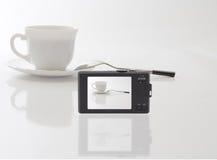 Η συμπαγής ψηφιακή κάμερα φωτογράφισε το άσπρο φλυτζάνι Στοκ Φωτογραφίες