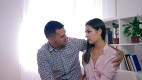 Η συμφιλίωση στην οικογένεια, ο ένοχος σύζυγος και η σύζυγος βάζουν επάνω μετά από τη φιλονικία και αγκάλιασμα στο φωτεινό δωμάτι απόθεμα βίντεο