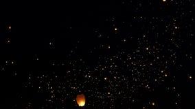 Η συναρπαστική άποψη σχετικά με το φωτεινό oarnge άναψε τα κινεζικά φανάρια εγγράφου κεριών που επιπλέουν αργά στο σκοτεινό μαύρο φιλμ μικρού μήκους