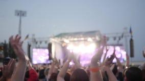 Η συναυλία βράχου, επιδοκιμασμένα ανεμιστήρες όπλα στη συναυλία, πολλοί άνθρωποι χτυπά τα χέρια τους, ακροατήριο υπαίθρια απόθεμα βίντεο