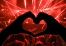 Η συναυλία μουσικής, χέρια που αυξήθηκαν με μορφή της καρδιάς για τη μουσική, θόλωσε το πλήθος και τους καλλιτέχνες στη σκηνή στο Στοκ Εικόνες