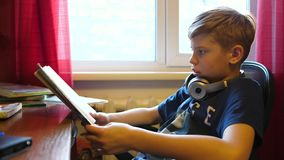 Η συνεδρίαση αγοριών στο σχολικό γραφείο και κάνει την εργασία Σχολική εκπαίδευση Ανάγνωση των βιβλίων απόθεμα βίντεο