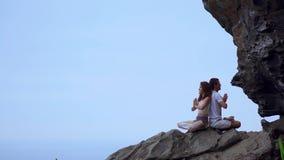 Η συνεδρίαση ανδρών και γυναικών πάνω από ένα βουνό σε ένα πλάτη με πλάτη meditate βράχου και κάνει τη γιόγκα στο υπόβαθρο του ωκ φιλμ μικρού μήκους