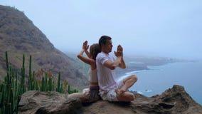 Η συνεδρίαση ανδρών και γυναικών πάνω από ένα βουνό σε ένα πλάτη με πλάτη meditate βράχου και κάνει τη γιόγκα στο υπόβαθρο του ωκ απόθεμα βίντεο
