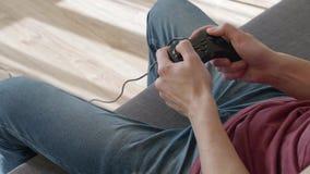 Η συνεδρίαση ατόμων στον καναπέ και παιχνίδι στο τηλεοπτικό παιχνίδι φιλμ μικρού μήκους