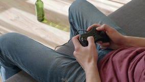 Η συνεδρίαση ατόμων στον καναπέ και παιχνίδι στο τηλεοπτικό παιχνίδι απόθεμα βίντεο