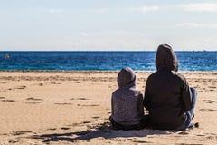 Η συνεδρίαση γιων και μητέρων γυρίζει πίσω στην παραλία και εξέταση τη θάλασσα στοκ εικόνα με δικαίωμα ελεύθερης χρήσης