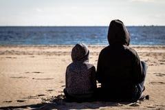 Η συνεδρίαση γιων και μητέρων γυρίζει πίσω στην παραλία και εξέταση τη θάλασσα στοκ φωτογραφία με δικαίωμα ελεύθερης χρήσης
