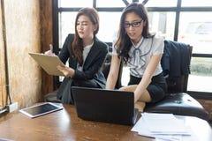 Η συνεδρίαση γυναικών δύο επιχειρήσεων και βλέπει το έγγραφο σε διαθεσιμότητα και τον υπολογιστή στον πίνακα στοκ εικόνα με δικαίωμα ελεύθερης χρήσης