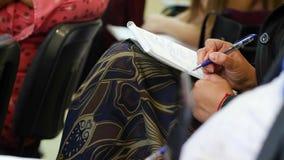 Η συνεδρίαση γυναικών στη διάσκεψη γράφει κάτι σε μια κινηματογράφηση σε πρώτο πλάνο σημειωματάριων απόθεμα βίντεο