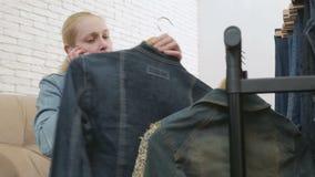 Η συνεδρίαση γυναικών στον καναπέ μιλά στο τηλέφωνο και επιθεωρεί μια συλλογή των τζιν που κρεμούν στην κρεμάστρα φιλμ μικρού μήκους