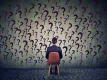 Η συνεδρίαση επιχειρησιακών ατόμων σε μια καρέκλα μπροστά από έναν τοίχο έχει πολλές ερωτήσεις, αναρωμένος τι να κάνει έπειτα Στοκ φωτογραφία με δικαίωμα ελεύθερης χρήσης