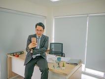 Η συνεδρίαση επιχειρησιακών ατόμων σε το δίσκο του και ελέγχει το κινητό τηλέφωνό του, στοκ εικόνα