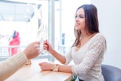 Η συνεδρίαση ζευγών αγάπης σε έναν καφέ, συζήτηση και πίνει τη σαμπάνια Στοκ Φωτογραφία