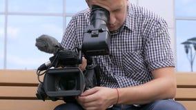 Η συνεδρίαση καμεραμάν σε έναν πάγκο κοντά στο κτήριο σε μια τηλεοπτική κάμερα απόθεμα βίντεο