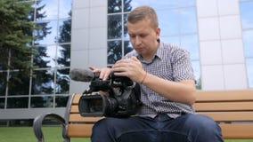 Η συνεδρίαση καμεραμάν στον πάγκο κοιτάζει βιαστικά το μήκος σε πόδηα στη τηλεοπτική κάμερα φιλμ μικρού μήκους