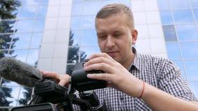 Η συνεδρίαση καμεραμάν στον πάγκο κοιτάζει βιαστικά το μήκος σε πόδηα στη τηλεοπτική κάμερα απόθεμα βίντεο