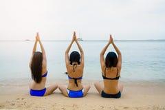 Η συνεδρίαση κοριτσιών γιόγκας στο λωτό θέτει στην παραλία στοκ φωτογραφία με δικαίωμα ελεύθερης χρήσης